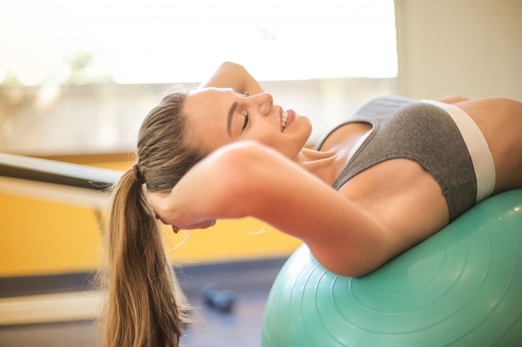 """alt=""""A lovely lady smiling while exercise with a medicine ball to boost her mental health and physical fitness."""""""
