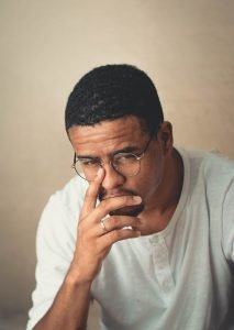 """alt=""""A light skin man in glasses buried in thought with slight fear and anxiety."""""""