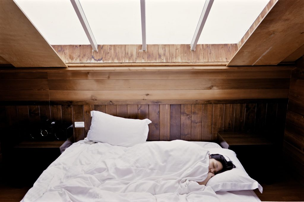 """alt=""""A beautiful wooden designed room with a lady sleeping on under a white sheet."""""""
